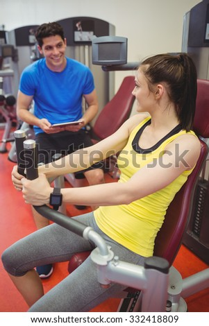 Fit woman using weights machine with trainer at the gym - stock photo