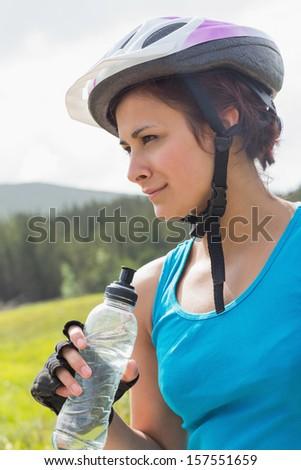 Fit woman wearing bike helmet holding water bottle in the countryside - stock photo