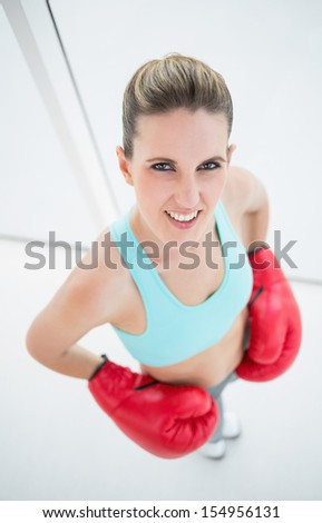 Fit woman wearing boxing gloves looking at camera