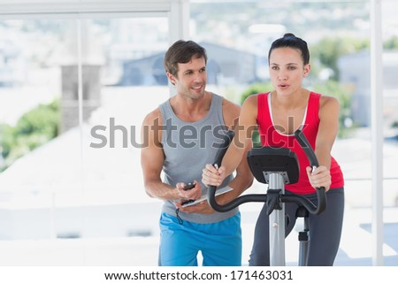 Fit woman with male instructor working out at class in a bright gym - stock photo