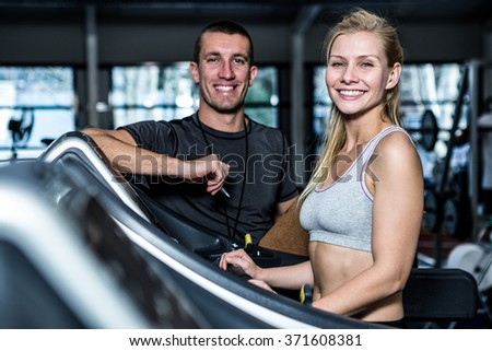Fit woman with trainer using treadmill at gym - stock photo