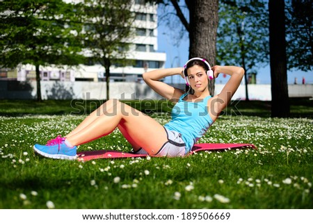 Fit woman working out doing sit ups fitness exercises in city park on spring or summer. Beautiful fitness girl during crunches workout.