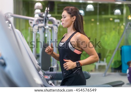 Fit woman working out jogging on treadmill at a gym - stock photo
