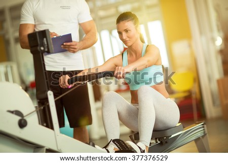 Fit woman working out on row machine her trainer taking notes in gym - stock photo