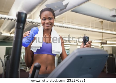 Fit woman working out on the cross trainer at the gym - stock photo