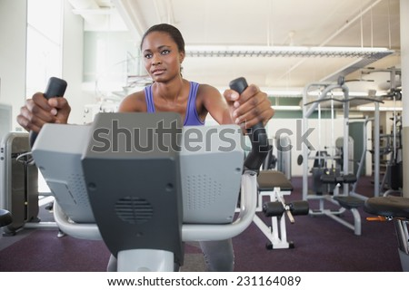 Fit woman working out on the exercise bike at the gym - stock photo