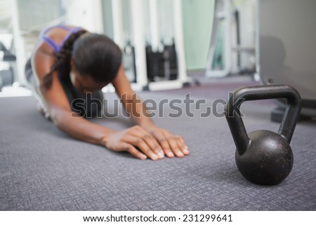 Fit woman working out with kettlebell at the gym