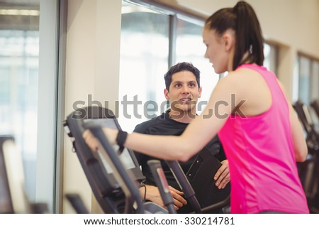 Fit woman working out with trainer at the gym - stock photo