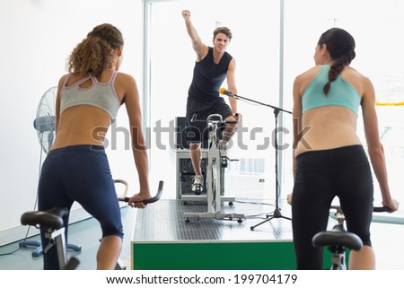 Fit women doing a fitness class with enthusiastic instructor at the gym - stock photo