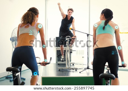 Fit women doing a spin class with enthusiatic instructor against fitness interface - stock photo