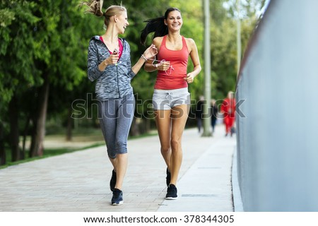 Fit women jogging outdoors and living a healthy lifestyle - stock photo