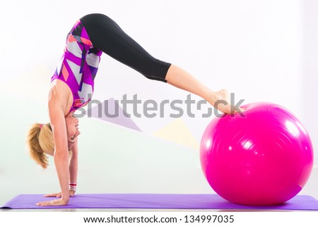 Fit young blonde pilates instructor showing different exercises with basic sport equipment including ball and yoga mat - stock photo
