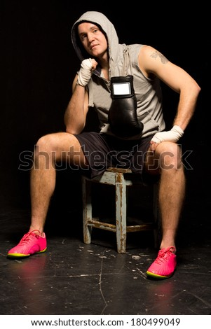 Fit young boxer sitting waiting for a fight on a wooden stool with his hands bandaged and his gloves slung around his neck as he stares thoughtfully into space - stock photo