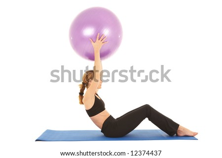 Fit young brunette pilates instructor showing different exercises on a white background with basic pilates equipment including a ball and yoga mat. White background, not isolated