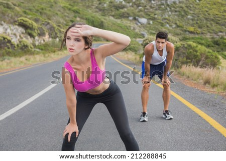 Fit young couple running on the open road together - stock photo