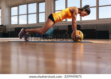 Fit young female athlete working out on her core muscles. Muscular woman exercising on fitness mat doing push ups with kettlebell. - stock photo
