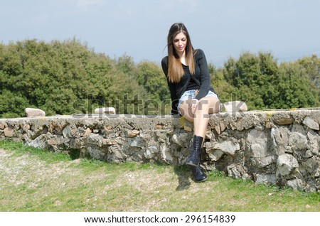 Fit young girl wearing sweater and shorts sitting with crossed legs and look at the camera