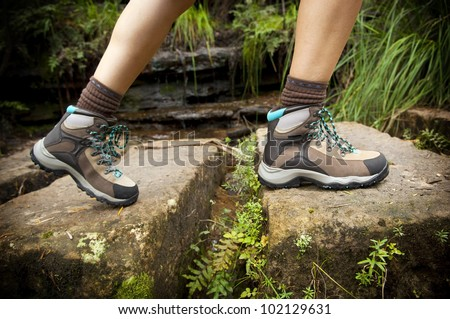 Fit young hiker crosses stone steps in hiking boots