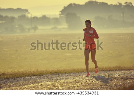 Fit young lady in red summer sportswear running, jogging on a country road while listening to music in earphones, early in the morning. Calories burning. Health care. Willingness concept. - stock photo