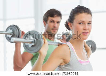 Fit young man and woman lifting barbells in the gym - stock photo