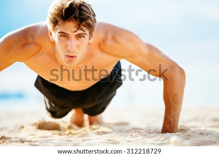 Fit young man doing push-ups on beach. Outdoor beach workout. Handsome young fitness man excessing. Sports and active lifestyle fitness concept.