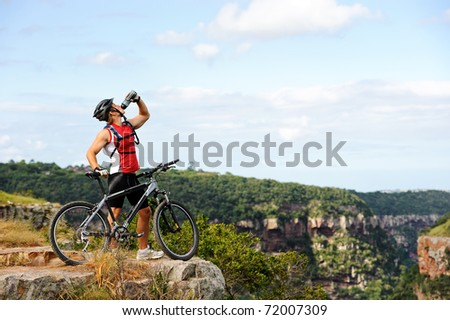 fit young man enjoys a thirst quenching drink after a mountainbike ride - stock photo