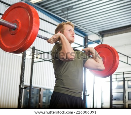 Fit young man lifting barbell at gym - stock photo