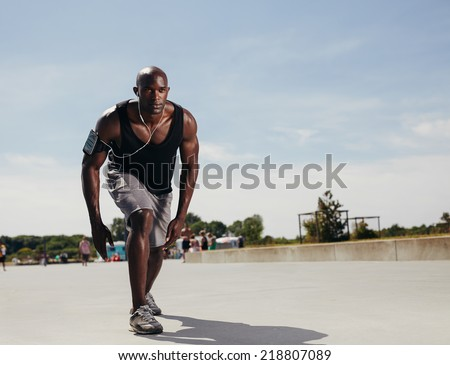 Fit young man on his mark to start running. Determined athlete outdoors. Muscular african male model ready for his run on a hot summer day. - stock photo