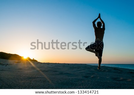 Fit young man practices sun salutation yoga on the beach at sunset - stock photo