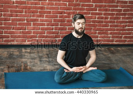 Fit young man with a beard wearing black T-shirt and blue trousers doing yoga position lotus asana and hands in mudra on blue matt at wall background, copy space, portrait, meditation - stock photo