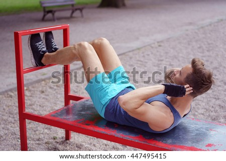 Fit young man working out outdoors doing sit ups on a red metal bench in a park - stock photo