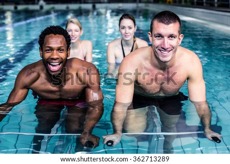 Fit young people cycling in the pool - stock photo