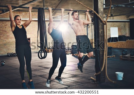 Fit young people doing pullups looking determined, working out in a gym - stock photo