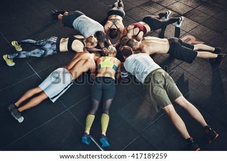 Fit young people focused on planking in a circle in a gym - stock photo