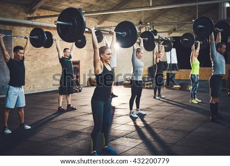 Fit young people lifting barbells looking focused, working out in a gym  - stock photo