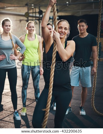 Fit young people standing around a rope in a gym looking positive - stock photo