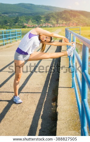 Fit young sporty blonde Caucasian teenage woman stretching legs after running outdoors on sunny summer day. Vertical, mild retouch, no filter. - stock photo