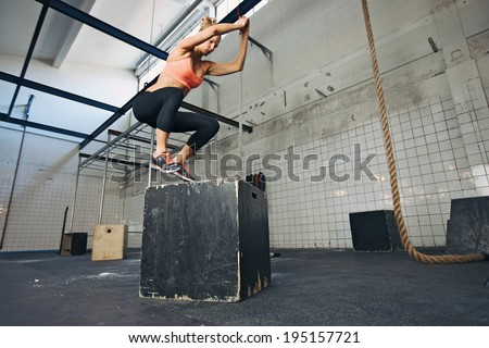 Fit young woman box jumping at a crossfit style gym. Female athlete is performing box jumps at gym. - stock photo