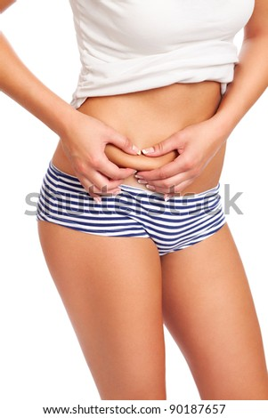 Fit young woman checking her belly fat, isolated on white