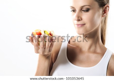 Fit young woman eating fruit salad - stock photo