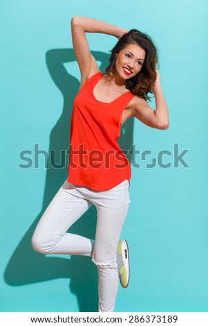 Fit Young Woman. Happy young woman in jeans and red shirt standing on one leg and holding hand behind head. Three quarter length studio shot on teal background. - stock photo