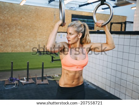Fit young woman holding gymnast rings at the gym looking away. Young caucasian woman exercising at gym. - stock photo