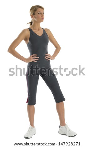 Fit young woman in sports clothing with hands on hips looking away against white background