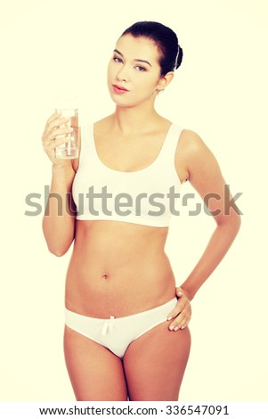 Fit young woman in underwear with glass of mileral water - stock photo