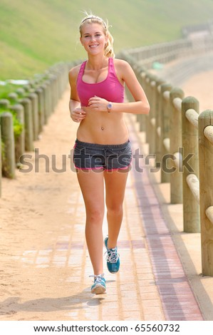 Fit young woman jogging on a pathway - stock photo