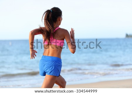 Fit young woman jogging on beach against sky. Rear view of determined female is in sports clothing. Runner is exercising at sea shore during sunny day. - stock photo