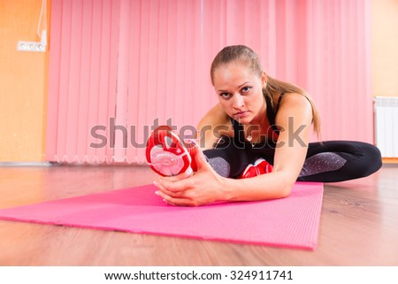 Fit Young Woman Looking at the Camera While Stretching her Leg on Top of a Fitness Mat Inside the Studio. - stock photo