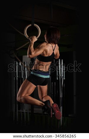 Fit young woman on gymnast rings in the gym - stock photo