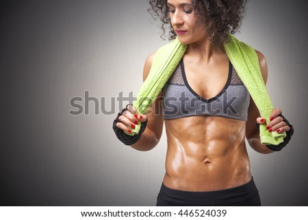 Fit young woman posing with a green towel on grey background - stock photo