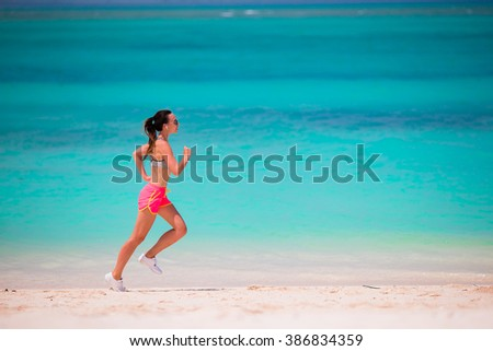 Fit young woman running along tropical beach in her sportswear